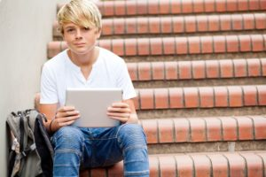 13738650 - teen boy sitting on stairs and using tablet computer in school